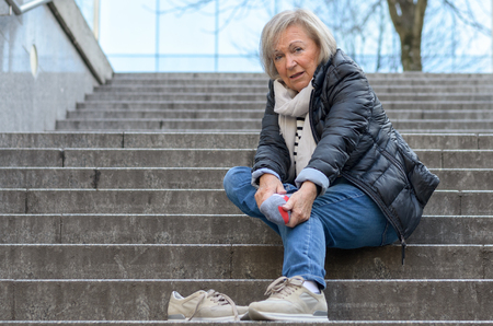 relive: Helpless senior woman massaging her Foot to relive aches and pains after falling down steps