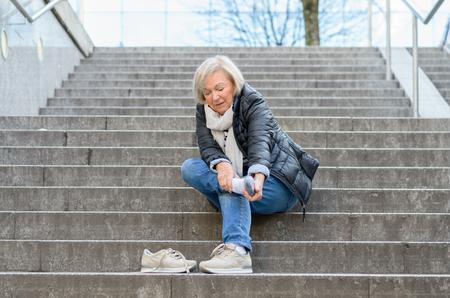 Mujer mayor indefensa masajear su pie para revivir dolores y molestias después de caer por las escaleras