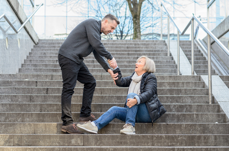 overthrown: Man helping senior woman to get up while she is sitting on stairs outdoors in the city, holding her knee
