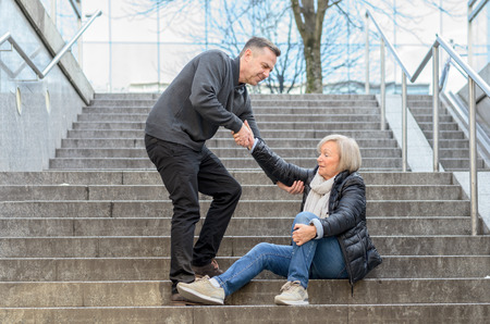 middle joint: Man helping senior woman to get up while she is sitting on stairs outdoors in the city, holding her knee