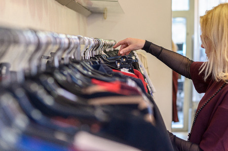 Female shopper searching through garments displayed on a rail in a clothing store or fashion boutique, close up side view of her hand and head
