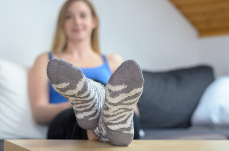Young blond woman relaxing with feet up on table wearing socks, focus on foreground