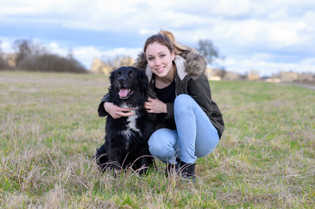 Happy young woman hugging her beloved black dog as they sit side by side in a rural field smiling at the camera Stock Photo
