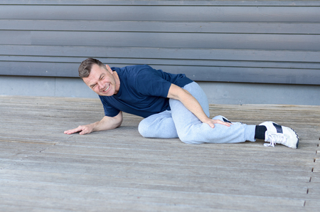 Sporty middle-aged man with muscle cramps in his calf lying on the floor clutching his leg and grimacing in pain