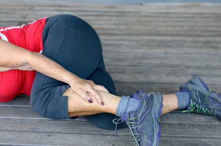 Fit sporty senior woman suffering from lower leg cramps during a workout clutching her calf in pain, close up view of her lower body lying on a wooden floor or deck