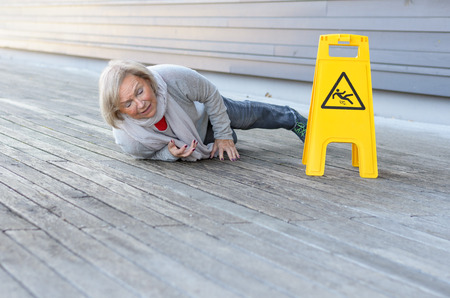 Senior lady slipping and falling on a wet surface with a grimace of pain right alongside a yellow warning sign in German, with foreground copy space