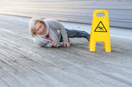 Senhora sênior escorregando e caindo sobre uma superfície úmida com uma careta de dor ao lado de um sinal de aviso amarelo em alemão, com espaço de cópia em primeiro plano Foto de archivo - 74355758