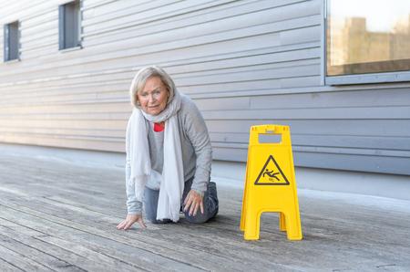 Oudere vrouw kruipend op haar knieën en grimmende in pijn na het glijden en vallen op een nat houten dek naast een fel geel waarschuwingsbord