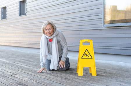 Elderly woman crawling on her knees and grimacing in pain after slipping and falling on a wet wooden deck alongside a bright yellow warning sign