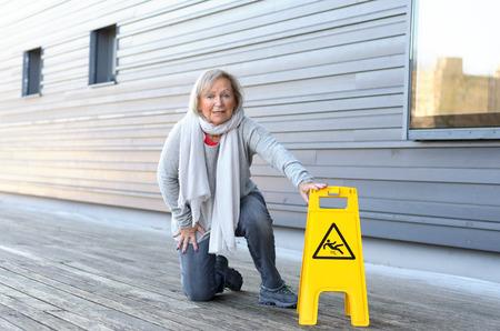 Mujer mayor que se inclina en sus rodillas y muecas en dolor después de deslizamiento y cayendo en una pared de madera oscura junto a una advertencia de hielo amarillo Foto de archivo - 74355766