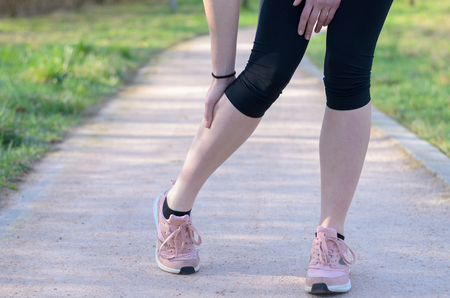 Young woman jogger suffering from calf muscle spasm or cramps bending down to clutch her leg in her hand as she runs along a pathway through grassy fields, low angle view of her legs