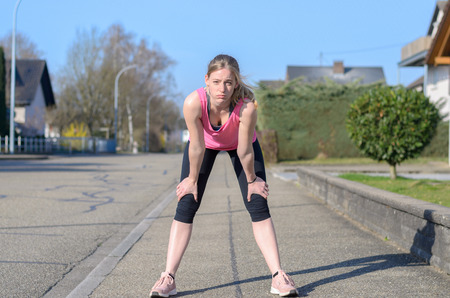 Fit young woman pausing for a break while out jogging and training along an urban road bending forwards with her hands on her knees looking at the camera in a health and fitness concept