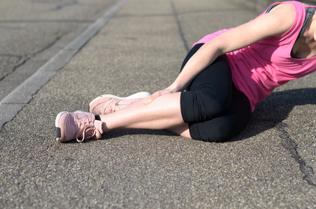 Female athlete with calf cramps lying on the sidewalk of a tarred road clutching her lower leg muscles in agony