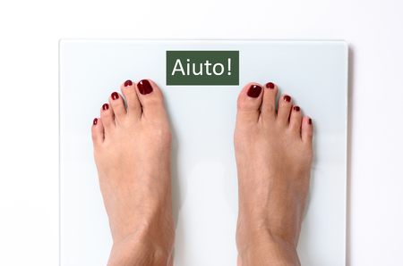 painted toenails: Close-up of incognito woman feet with red nail polish standing on white weight scales with word Aiuto on screen Stock Photo