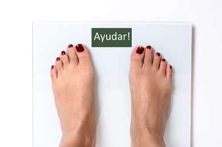 painted toenails: Close-up of incognito woman feet with red nail polish standing on white weight scales with word Ayudar on screen Stock Photo
