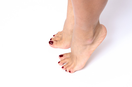 painted toenails: Woman with stylish colorful red varnished toenails after a pedicure and spa treatment standing on tiptoe on a white background Stock Photo
