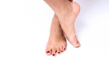 painted toenails: Beauty concept of red painted toenails after a spa treatment and pedicure with a close up view on female feet over a white background Stock Photo