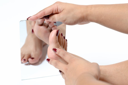 Woman admiring her feet in a mirror with colorful red painted toenails after a treatment in a spa and pedicure in a close up view of her feet and reflection