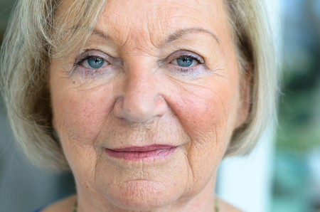 Close up cropped view of the face of an attractive senior woman with fair hair, blue eyes and wrinkled skin looking directly into the camera with a calm expression