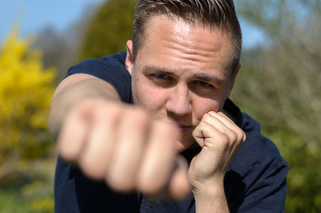 Determined young man punching at the camera with his clenched fist with focus to his face and resolute expression outdoors in a garden Stock Photo