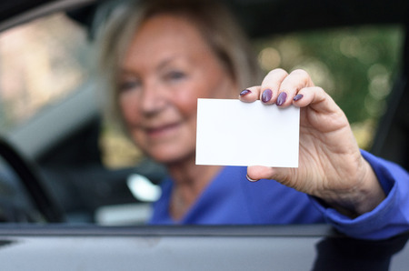 drivers seat: Elderly woman leaning through the open window from the drivers seat of a car showing her licence with a happy friendly smile