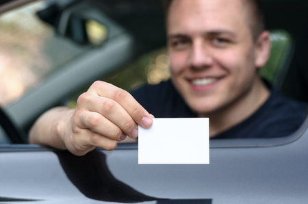 drivers seat: Young man leaning through the open window from the drivers seat of a car showing his licence with a happy friendly smile
