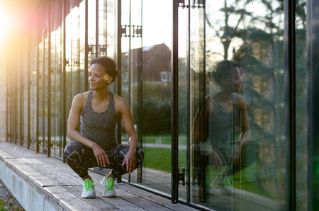 physique: Side View of a Young african woman while she is sitting in the squat