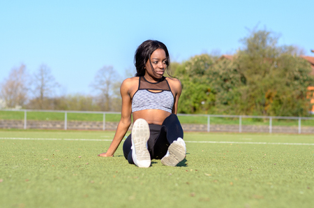 Fit athletic young woman relaxing on a sports field sitting in black legging with her legs stretched out in front of her watching something to the side