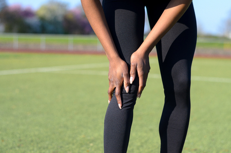 Sporty muscular young woman in tights standing on a sports field clutching her knee after injuring her joint , close up on her legs and hands