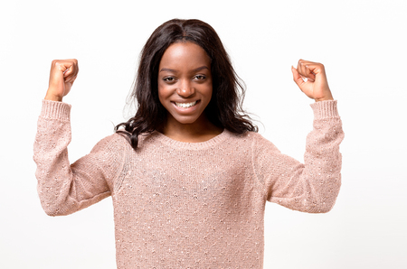 Exuberant exultant young African woman cheering a victory, success or win punching the air with her fists and laughing over white with copy space