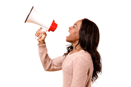 Angry young African woman yelling into a megaphone as she makes her grievances known at a demonstration or rally, side view on white Banco de Imagens - 76932593