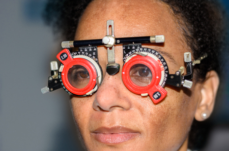 afroamerican: Young African woman at an eye test in a hospital