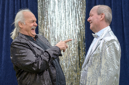 Jovial performer with his grey hair in a ponytail pointing and having a good laugh at his friend in a silver jacket and bow tie during a live stage performance Stock Photo