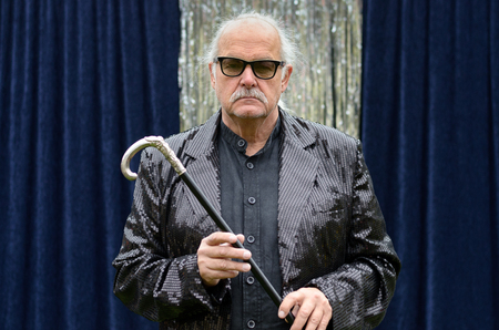 Deadpan stage performer in heavy rimmed glasses and jacket standing in front of blue curtains holding a silver topped cane looking expressionlessly at the camera