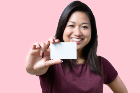 Smiling young Chinese woman holding up a blank white business card on display in a concept of identification, qualifications, contact or branding, focus on card