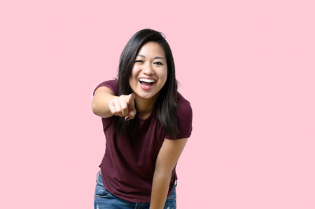 Laughing vivacious young Chinese woman pointing at the camera while bending forwards with a happy expression isolated on pink Reklamní fotografie