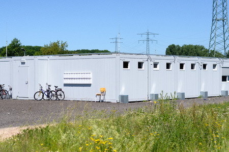 Prefabricated white metal housing for workmen on site with parked bicycles leaning on the walls and a power pylon in the background