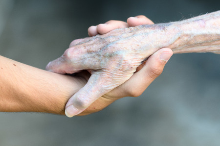 Old and young man shaking or gripping hands in a close up view conceptual of assistance, agreement, acceptance, greeting and tolerance Stock Photo