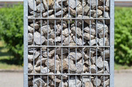 Steel mesh container filled with stones and rocks outdoors in a garden in a close up side view