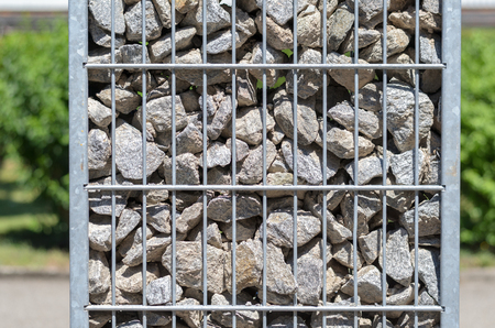 wire mesh: Steel mesh container filled with stones and rocks outdoors in a garden in a close up side view