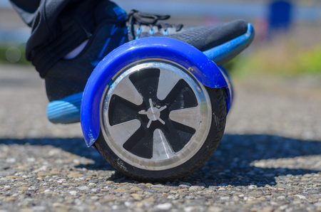 Person riding a hover board in a close up low angle view of the wheel and a foot in a sneaker