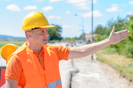 Young construction worker signalling with his hand showing a car an alternate route as he stands in front of a warning chevron for roadworks on a rural road