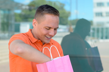 Happy young man delving in a shopping bag with his hand smiling in anticipation of the contents reflected in a large window on a commercial building
