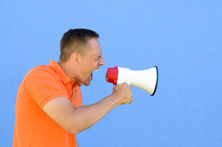 Man in orange shirt screaming through the megaphone with his eyes shut, standing against plain blue background with copy space, shot from the side