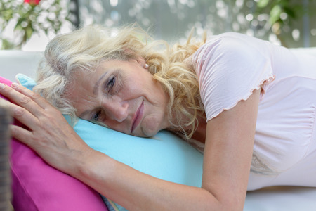 recuperating: Exhausted or unwell senior woman taking a rest lying on her stomach on a sofa at home looking at the camera with a serious expression