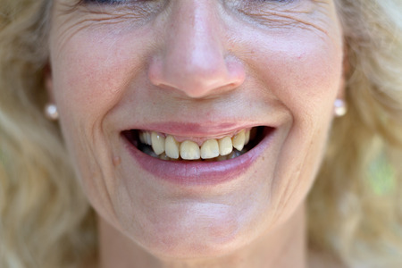 Cropped face of a happy smiling senior woman wearing light makeup in a close up view of her smiling mouth and upper teeth in a beauty, skincare and ageing concept Stock fotó