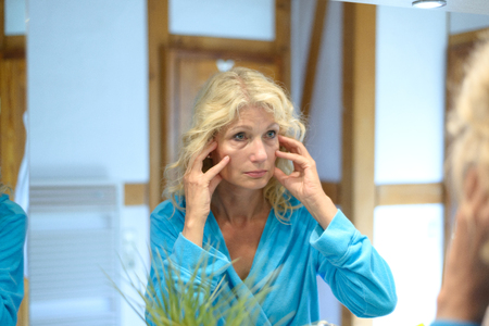 pinching: Senior woman checking her wrinkles in a mirror using her fingers to stretch the skin over her cheeks and eyes to simulate a face-lift