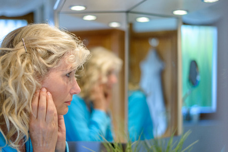 Middle-aged woman looking at herself in a mirror with her hands to her cheeks as she considers the ageing process with multiple reflections Stock Photo