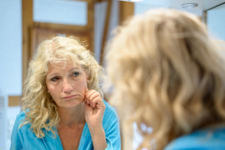 Mujer rubia mayor que revisa su piel envejecida en un espejo tirando de ella a un lado sobre sus mejillas mientras ella considera cuidadosamente el efecto en sus características