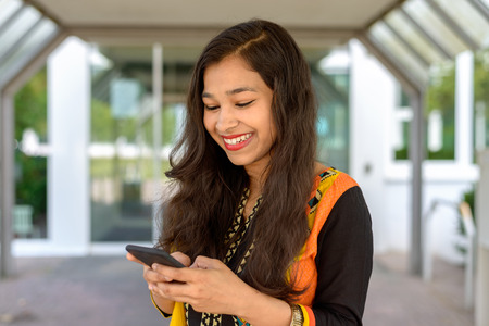 Young Indian woman smiling as she reads a text message on her mobile phone while standing outdoors in an urban environment